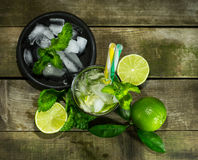 Mojito with ice on wooden background. Glass with Mojito and crushed ice on wooden background stock photo