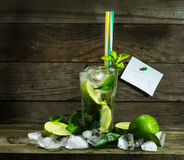 Mojito with ice on wooden background. Glass with Mojito and crushed ice on wooden background royalty free stock photo
