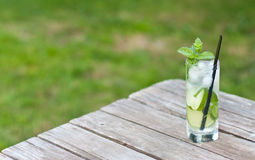 Mojito on a picnic table. Mojito served on a picnic table on a nice sunny day with green grass Royalty Free Stock Photo