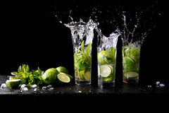 Mojito summer beach refreshing tropical cocktail splash in glass highball alcohol drink with soda water, lime juice. Mint leaves, sugar, ice and rum. Dark royalty free stock photos