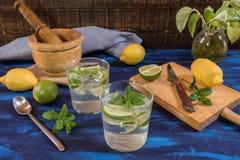 Mojitococktail met zijn ingrediënten op een blauwe lijst royalty-vrije stock afbeeldingen