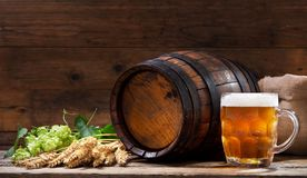 Mok bier met groene hop en tarweoren stock afbeeldingen