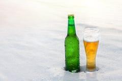 Mok en fles koud bier in de sneeuw bij zonsondergang Mooie de winterachtergrond Openlucht recreatie royalty-vrije stock foto