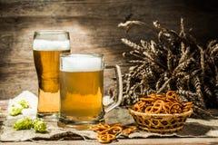 Mok, glas schuimend bier op lege houten achtergrond Stock Foto's