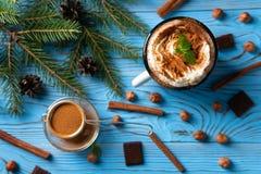 Mok met hete die chocolade en slagroom, met grondkaneel en muntbladeren op een blauwe houten lijst wordt verfraaid royalty-vrije stock foto's