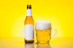 Mok met schuimend bier en lege fles Royalty-vrije Stock Afbeelding