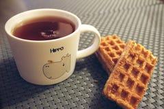 mok met thee en wafels stock afbeelding
