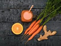 Mok met wortel smoothie, gemberwortel en sinaasappel op houten lijst De mening vanaf de bovenkant Vlak leg Stock Foto's