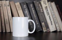 Mok op het boekenrek Stock Foto's