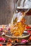Mok thee met roze bloemblaadjes Stock Afbeelding