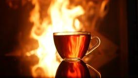 Mok thee op de achtergrond van het branden van open haardvlam stock video