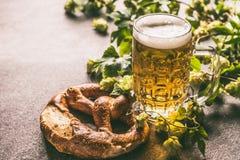 Mok van bier en pretzel met wijnstok en kegels van hop royalty-vrije stock foto