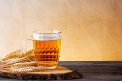 Mok van lichte bier en tarweoren op de houten lijst Stock Afbeeldingen