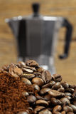 Moka express coffee maker 2. Image of an Italian Moka Express stovetop coffee maker behind coffee beans and grinds. Shallow depth of field - focus is on top royalty free stock photos