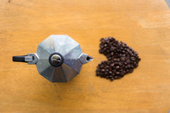 A moka pot and a cup of coffee with roasted coffee beans Royalty Free Stock Image