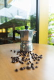 A moka pot and a cup of coffee with roasted coffee beans Stock Images