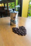 A moka pot and a cup of coffee with roasted coffee beans Stock Photo