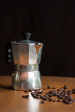 A moka pot and a cup of coffee with roasted coffee beans Stock Image