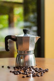 A moka pot and a cup of coffee with roasted coffee beans Royalty Free Stock Photo