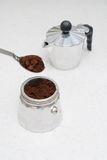 Moka pot and grinded coffee. On a white table Stock Image