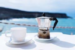 Moka-Topfespressohersteller und -Tasse Kaffee auf Tabelle mit Küstenlinie und -ozean im Hintergrund lizenzfreies stockbild