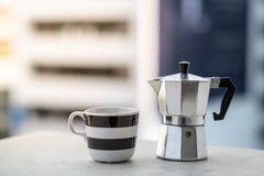 Mokapot y fondo de la ciudad de la taza y de la falta de definición de café imagen de archivo