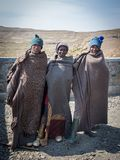 Mokhotlong, Lesotho - September 11, 2016: Three unidentified young African sheperds in traditional thick blankets stock images