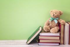 Mokietu niedźwiedź z stertą książka na zielonym tle kosmos kopii Obrazy Stock