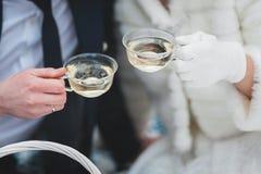 Mokken met thee in de handen van de bruid en de bruidegom in de winter royalty-vrije stock foto