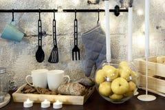 Mokken op de lijst in de keuken Mandarijnen in een glasvaas Heel wat kaarsen familievakantie in de keuken De dag van de valentijn stock afbeelding