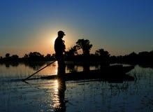 Mokoro sunset. An adventurer poles his mokoro across the Okavango Delta, in Botswana Stock Photos