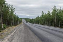 Mokra asfaltowa droga otaczająca lasem zachmurzone niebo Obrazy Stock