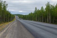Mokra asfaltowa droga otaczająca lasem zachmurzone niebo Obraz Royalty Free