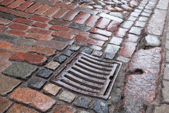 Mokra drenaż pokrywa na kamiennym bruku zdjęcie royalty free