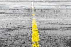 Mokra sterowanie śladu droga Z żółtym lampasem oddziela wskazywać na bruku Fotografia Stock