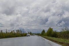 Mokra wiejska droga, i?? w odleg?o?? Woko?o zwartych g?szczy drzewa i krzaki zachmurzone niebo zdjęcie royalty free