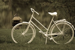 Mokre rocznika stylu spojrzenia białe kobiety rowerowe w mokrych gras na jeziorze obraz stock