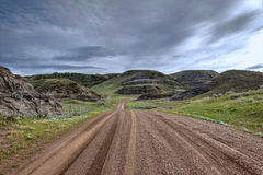Mokrego żwiru drogowy cewienie przez trawy zakrywał wzgórza pod burzowym niebem Zdjęcie Royalty Free