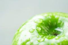 Mokry Dojrzały Zielony Organicznie Apple z wod kroplami na Jasnopopielatym tle Makro- Widoczna tekstura Kreatywnie Minimalistyczn fotografia royalty free