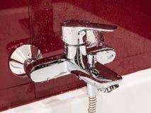 Mokry faucet zakrywający wodą opuszcza w nowożytnej łazience Fotografia Stock