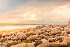 Mokry kamienia lata plaży zbliżenie z morza, góry i nieba tłem, zdjęcia stock