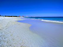 Mokry piasek odbija niebieskie niebo na Australijskiej plaży zdjęcia royalty free