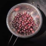 Mokrzy czerwoni agresty w metalu colander fotografia royalty free