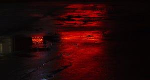 Mokrzy droga asfaltu odbicia, czerwone światło fotografia royalty free