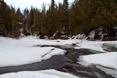 Mola adiantada em Minnesota do norte e no rio da cascata que mostram através do gelo e da neve foto de stock