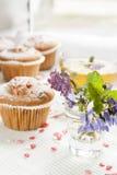 A mola azul floresce a viola, os queques e o copo do chá verde Foto de Stock Royalty Free
