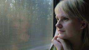 Mola e curso Uma mulher olha para fora a janela, vai pelo trem ou pelo carro video estoque