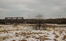 A mola, em alguns lugares l? s?o neve, a ponte de estrada de ferro sobre o rio, a vila imagem de stock royalty free