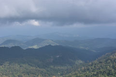 A mola escura do vale da montanha da névoa e da nuvem ajardina Fotos de Stock Royalty Free