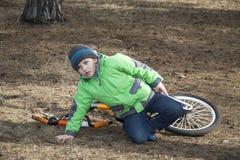 A mola no menino da floresta caiu sua bicicleta Fotos de Stock Royalty Free